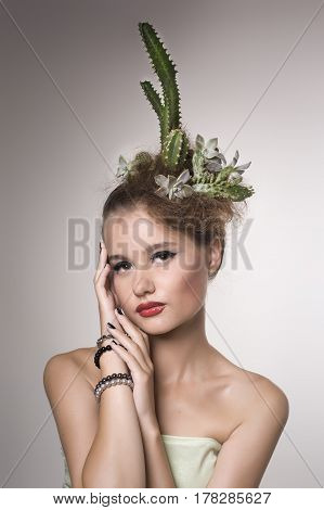 Woman with cactus in her hair on a gray background