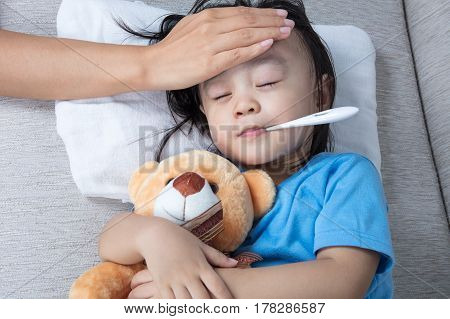 Asian Chinese Mother Measuring Little Girl Forehead For Fever