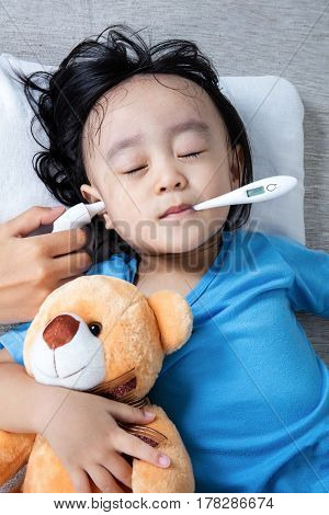 Asian Chinese Little Girl Getting Ear Measurement For Fever Temperature