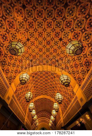 Islamic ornamental design on ceiling and a row of decorative lamps.