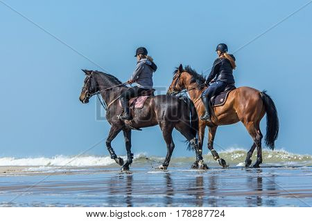 Kijkduin the Netherlands - March 24 2017: horseback riders enjoying the spring weather on the beach