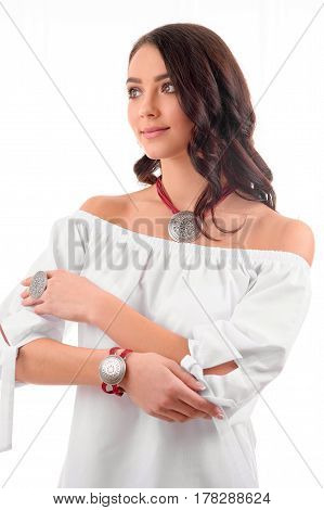 Beauty and Jewelry model woman in white dress modern style with long hairstyle and silver bijouterie. Gorgeous fashion brunet girl with necklace earrings in fashionable jewelry