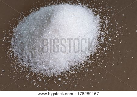 Heap of white granulated sugar on gray surface. Close-up