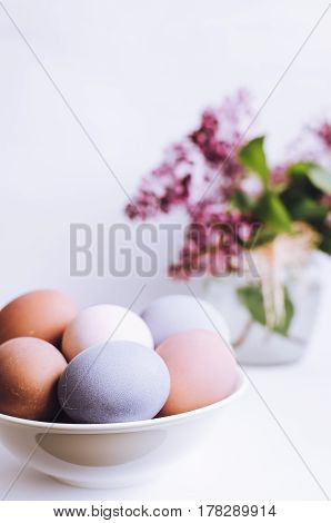 Easter background with handmade painted purple eggs and bouquet of lilac on a white background. Selective focus. Toned image.