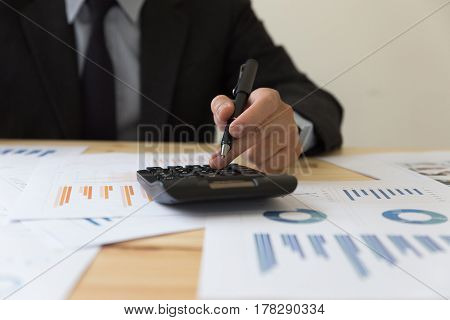 Businessman Analyzing Report On Chart With Calculator