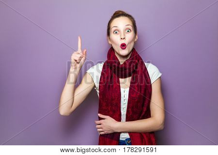 Idea portrait happy beautiful woman thinking looking up pointing with finger at blank copy space on purple background. Positive human face expressions emotions feelings body language.