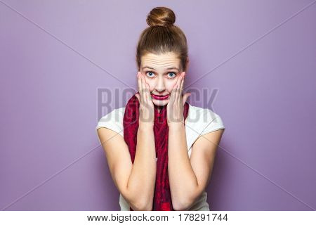 Unhappy mistake concept. portrait of a young cute woman with red scarf and freckles on her face unhappy emotional expression concept on purple background.