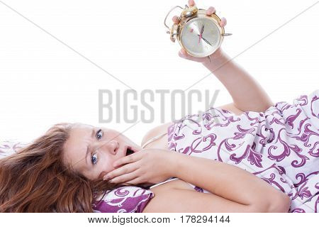 Woman waking up in the morning looking at the alarm clock is horrified that overslept