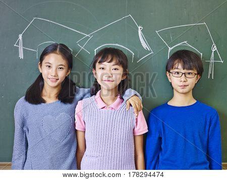 three asian elementary school children standing in front of chalkboard underneath chalk-drawn doctoral caps.
