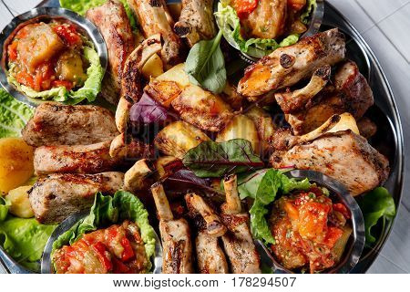 Meat plate with delicious pieces of meat salad ribs grilled vegetables and sauce. Top view.
