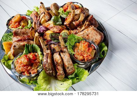 Meat plate with delicious pieces of meat salad ribs grilled vegetables potatoes and sauce on white wooden table.