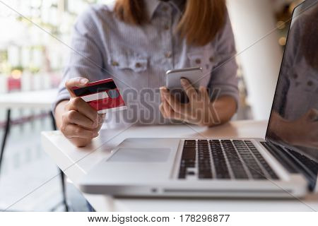 Woman Hands Holding Credit Card And Using Mobile Smart Phone For Online Shopping.