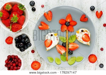 Summer food art for kids - edible picture on a plate with fresh berries