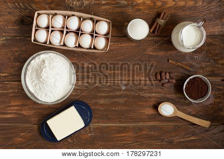 Ingredients for making cinnamon rolls on a wooden background . Flour , sugar, egg , chocolate , cocoa , cinnamon and butter. Close up. Top view