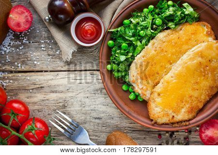 Wiener schnitzel with cheese and lettuce green peas salad top view