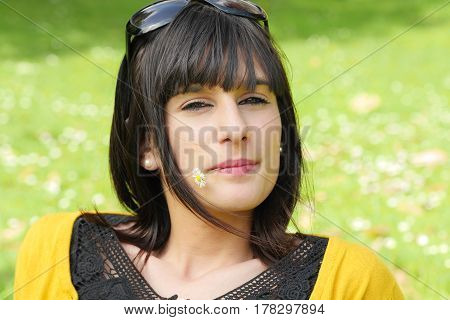 portrait of young smiling brunette girl in the park outdoors
