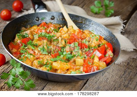 Vegetable saute in frying pan on a wooden background
