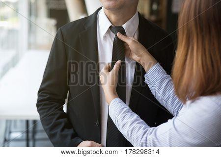 Woman Arranges Necktie Knot Of Man In A Suit