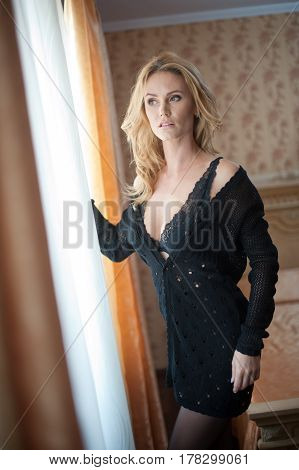 Young beautiful sexy woman in black bra and skirt posing in window light in vintage hotel room. Sensual blonde long hair female staying near a window. Attractive girl with transparent bra