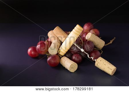Many wine corks and a vintage cork screw and red grape on a dark background.