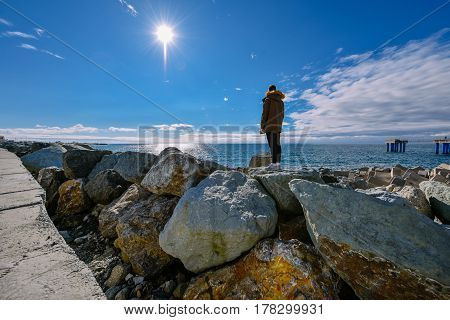 Young man traveller standing on natural stones and watching at sun over Black sea, Sochi, Russia. Rear view
