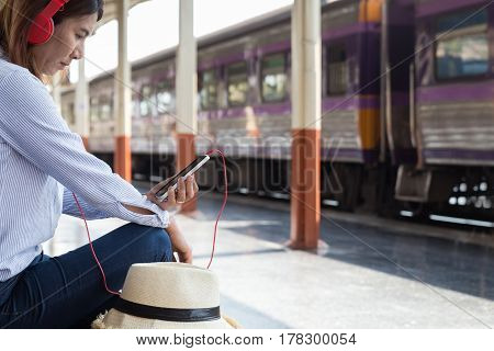 Young Woman Waiting On The Station Platform With Backpack On Train Station