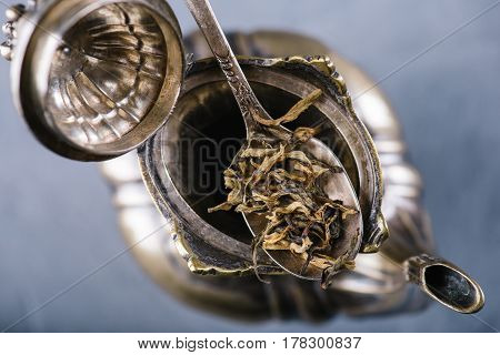 Dry green tea leaves in metal vintage spoon over open teapot, top view, selective focus, horizontal composition. Healthy clean eating lifestyle concept