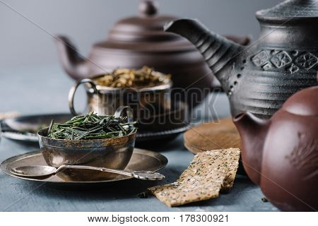 Dry green tea leaves in metal vintage bowl, crispy bread slices and clay teapots, selective focus, horizontal composition. Healthy clean eating lifestyle concept