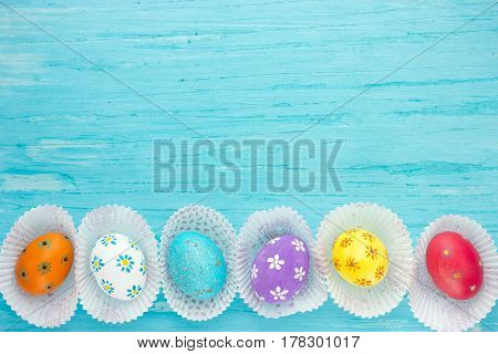 Colorful easter eggs on blue background with space
