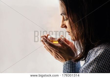 Yound dark haired woman holding glass of Fresh herbal tea with eyes closed, side view, copy space. Healthy lifestyle concept