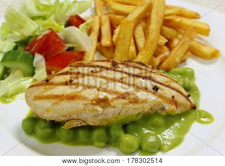 Grilled chicken breast on a bed of green pea puree and peas, served with a salad and french fried potato chips, side view