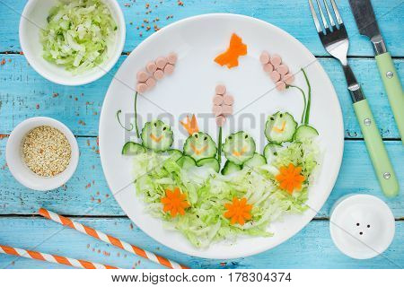 Creative idea for healthy food for kids - cucumber cabbage salad shaped funny frogs on a swamp