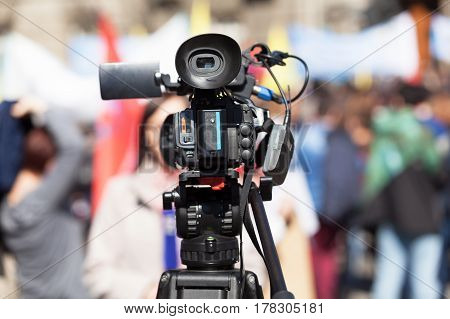 Filming female reporter with a video camera, blurred crowd in the background. TV broadcasting.