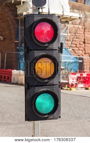 Confusing set of traffic lights showing red amber and green all at the same time can be used for concepts showing indecision mixed messages or conflicting signals or just a broken road light