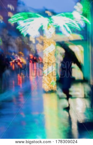 Lonely girl under an umbrella on the sidewalk next to an illuminated palm tree, city street in rain, bright reflections of street lamps. Intentional motion blur, Impressionism style. Concept of modern city.