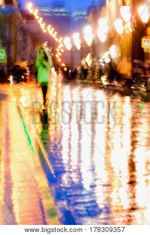 Abstract background of Girl in bright green coat. Bright reflections of street lamps in wet asphalt Intentional motion blur. Concept of seasons, weather, modern city.