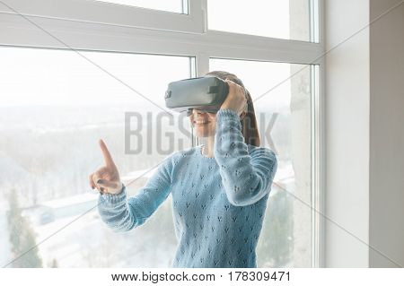 Beautiful young woman standing near a window in the smart home and looking into virtual reality goggles. Future technology concept. Modern imaging technology.