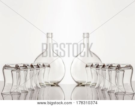 On a reflective tile is an empty transparent bottle and glass