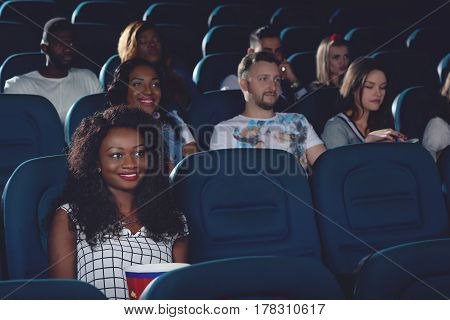 Pretty smiling african woman with curly hair and bright make up spending free time in cinema. Young girl sitting alone and watching funny movie in modern cinema hall. Group of people of background.