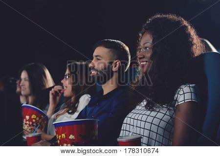 Side view of positive company of international people watching interested movie. Curly african girl toothy smiling and watching at projector in modern cinema hall.
