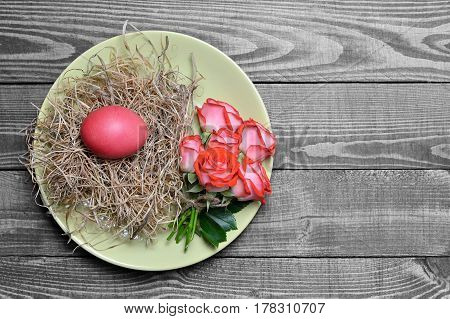 Easter table decoration: Plate decorated with Easter egg in the nest and flowers