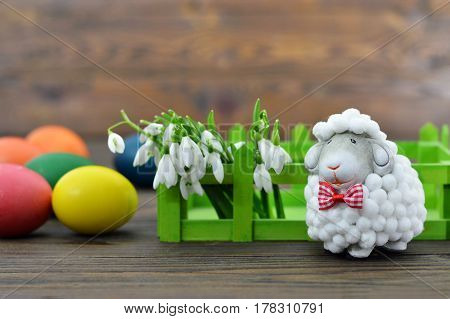 Easter eggs spring flowers and cute sheep figurine on wooden background