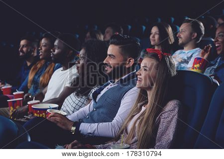 Side view of young women and men watching movie in modern cinema hall and smiling. Group of people eating popcorn and spending free time in cinema together.