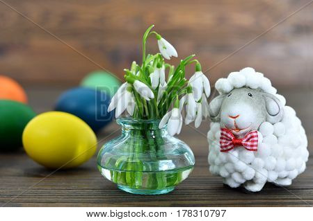 Easter eggs spring flowers and cute sheep figurine