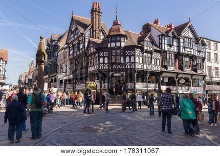 Chester England UK - March 25 2017: Shoppers and visitors on the corner of Eastgate and Bridge Street with the medieval stone cross in the historic city of Chester with its beautiful half timbered buildings