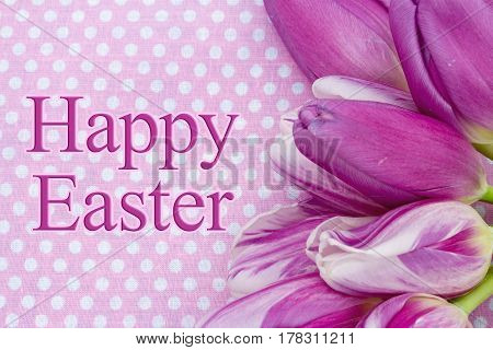 Happy Easter greeting A bouquet of purple tulips on pink polka dots with text Happy Easter