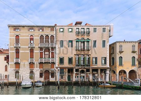 Old Gothic architecture houses in Venice with docked boats
