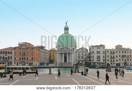 VENICE ITALY - JANUARY 09; Tourists walking around large square across the Grand Canal from San Simeone Piccolo church in Venice Italy - January 09 2017: San Simeone Piccolo faces the railroad terminal serving as entry point for most visitors to the city.