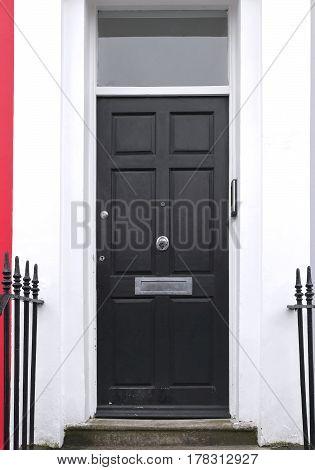 Black wooden entrance door exterior on retro residential house