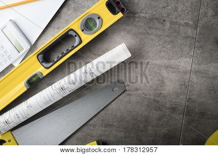 Architecture theme . Rolls with building projects, equipment of architect: crash helmet and spirit level on wooden table.